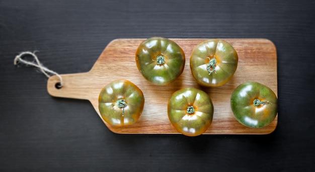 Organiczne pomidory black krim na drewnianej desce do krojenia