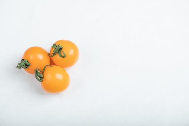 Organiczne pomidory czereśniowe na białym tle. . wysokiej jakości zdjęcie