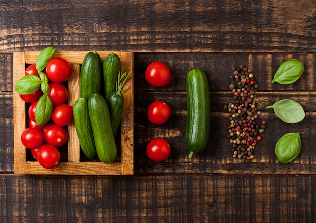 Organiczne pomidory i ogórek z bazylią i lnianym ręcznikiem w vintage drewnianym pudełku na drewnianym stole