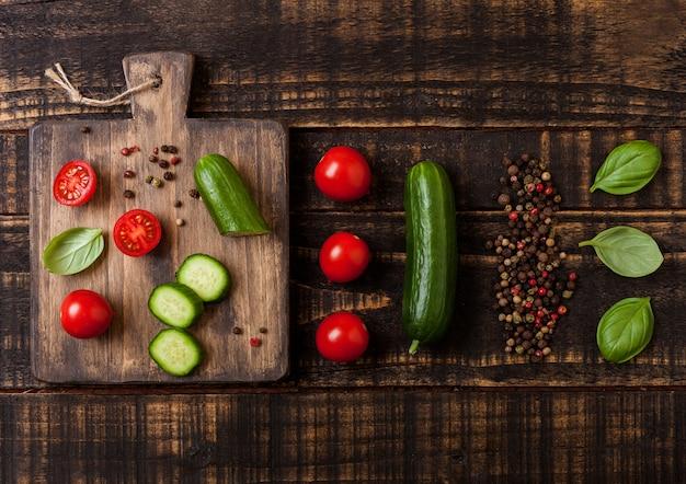 Organiczne pomidory i ogórki z bazylią i lnianym ręcznikiem na desce do krojenia na drewnianym stole w kuchni.