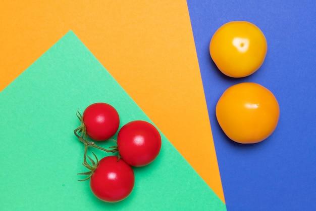 Organiczne pomidory w różnych kolorach na zielonym, pomarańczowym i niebieskim tle