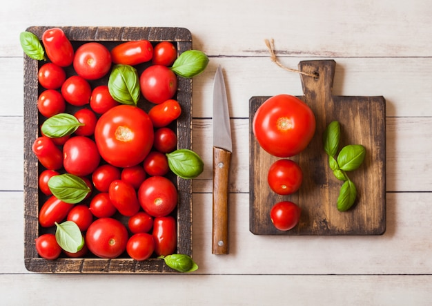 Organiczne pomidory z bazylią w vintage drewniane pudełko na drewnianym stole w kuchni