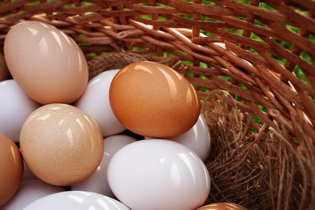 Organiczne rustykalne białe i brązowe jaja kurze zbliżenie na naturalnej tkaninie w koszu i żółtym małym c...
