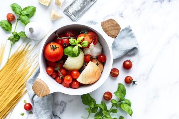 Organiczne składniki makaronu i warzywa w ceramicznym garnku