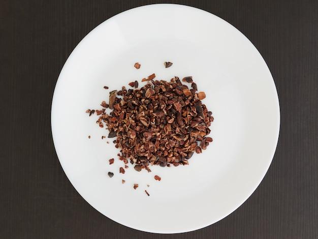 Organiczne stalówki kakao na białym talerzu. widok z góry.