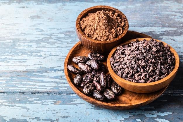 Organiczne surowe ziarna kakaowe, stalówki w drewnianych misach