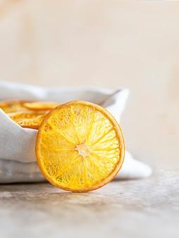 Organiczne suszone chipsy pomarańczowe w ekologicznej płóciennej torbie na jasnym tle betonu. selektywne skupienie.