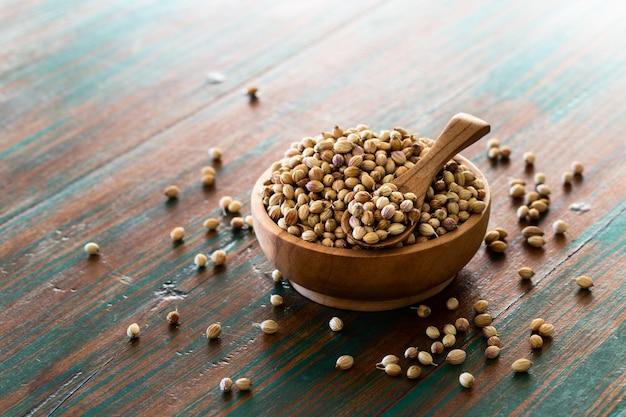 Organiczne suszone nasiona kolendry (coriandrum sativum) w drewnianej misce z łyżeczką.