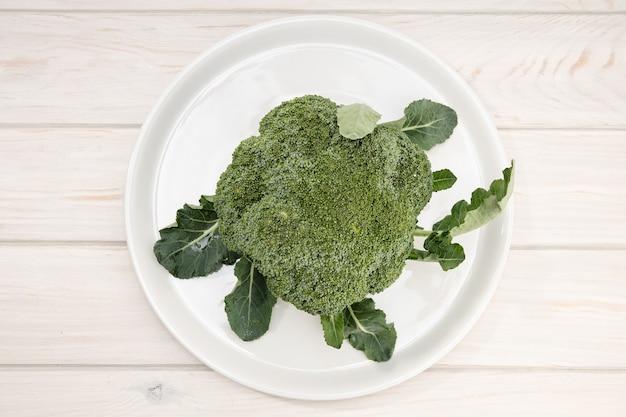 Organiczne świeże brokuły w talerzu na drewnianym stole. widok z góry. brassica oleracea