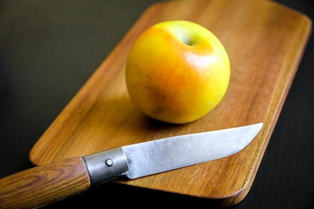 Organiczne świeże jabłko i scyzoryk na drewnianej desce do krojenia