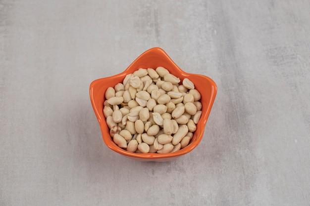 Organiczne świeże orzeszki ziemne w pomarańczowej misce.