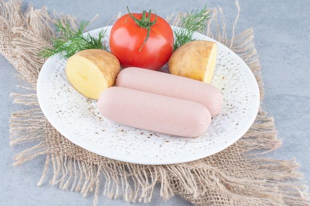 Organiczne warzywa i świeże kiełbasy na białym talerzu.