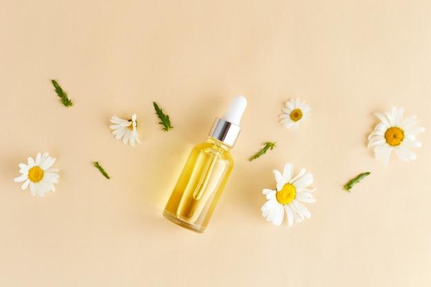 Organiczne wegańskie naturalne kosmetyki do włosów płaski układanie kompozycji kwiatów rumianku i butelek kosmetycznych z olejkiem eterycznym naturalne piękno widok z góry miejsce na tekst