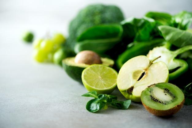Organiczne zielone warzywa i owoce na szarym tle. zielone jabłko, sałata, ogórek, awokado, jarmuż, limonka, kiwi, winogrona, banan, brokuły