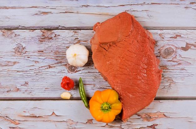 Organicznie czerwony surowy wołowina stku czosnku pieprz na drewnianym stole.