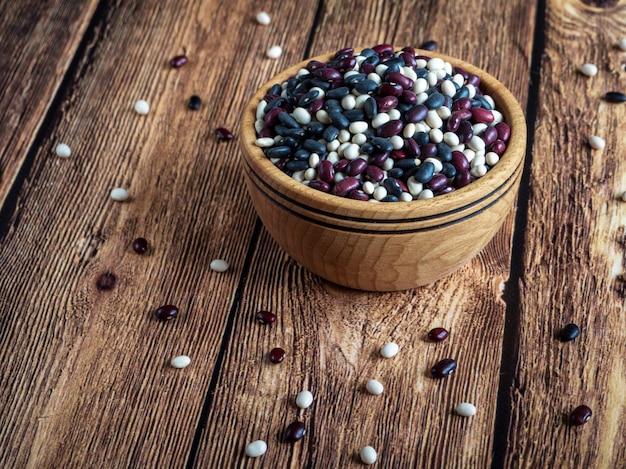 Organicznie fasole w talerzu na drewnianym stole. kolorowe fasole w drewnianym pucharze na nieociosanym drewnianym stole.