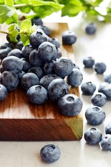 Organicznie jagodowe jagody na drewnianej desce. lato lekki deser jagody na szarym tle. zdrowe jedzenie. lato i zdrowie