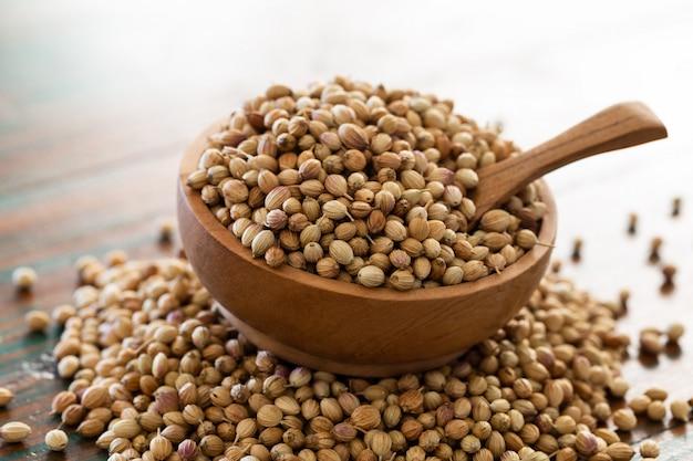 Organicznie suszone nasiona kolendry w drewniane miski z łyżeczką na kolorowym tle rustykalnym.