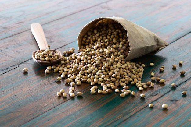 Organicznie suszone nasiona kolendry w papierowej torebce worek na kolorowym tle rustykalnym.