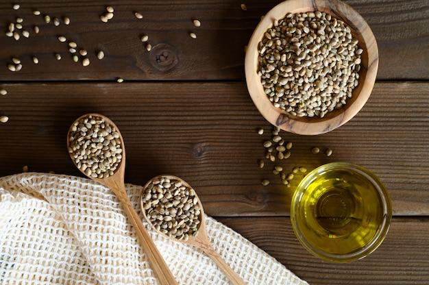 Organicznie suszone nasiona konopi w kompozycji z przedmiotami kuchennymi na drewnianym