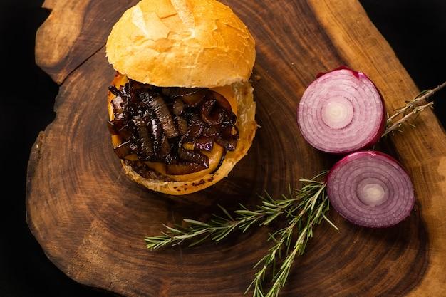 Organicznie wyśmienity burger dla smakoszy. hamburger z opiekanym i chrupiącym chlebem, topiącym serem, cebulą, rozmarynem zioło na drewnianym stole. widok z góry