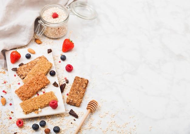 Organiczny batonik zbożowy z jagodami na marmurowej desce z łyżką miodu i słoikiem owsa i ręcznikiem na marmurowym stole.
