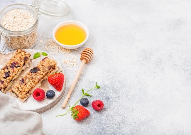 Organiczny batonik zbożowy z jagodami na okrągłej płycie vintage z łyżką miodu i słoikiem owsa na marmurowym stole. truskawka, malina i jagoda z liściem mięty