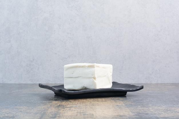 Organiczny biały ser na czarnym talerzu