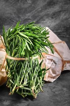 Organiczny bukiet świeżego rozmarynu na szarej powierzchni. pięknie zawiązana wiązka świeżej trawy. dostawa produktów, kopie przestrzeni.