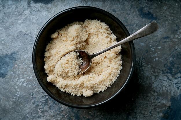 Organiczny cukier brązowy w misce łyżką nad szarym stołem. widok z góry. flat lay. skopiuj miejsce