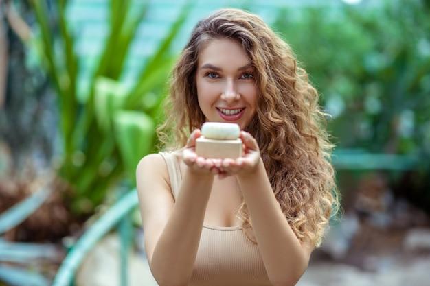 Organiczny. długowłosa kobieta w beżowym topie z kostką mydła