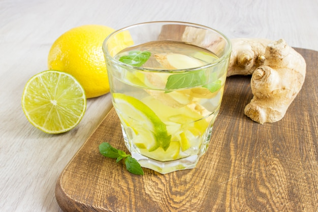 Organiczny imbirowy napój gazowany w szklance z cytryną i limonką