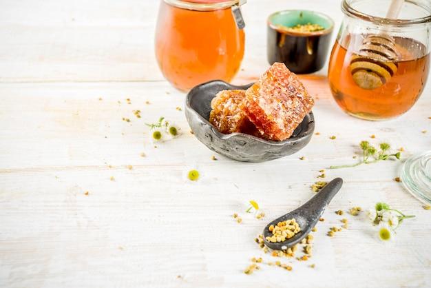 Organiczny kwiatowy miód, w słoikach, z pyłkami i plastrami miodu, na białym drewnianym stole, z polnymi kwiatami