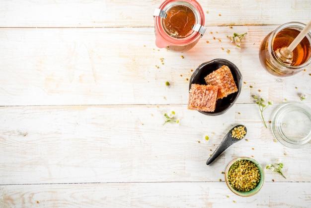 Organiczny kwiatowy miód, w słoikach, z pyłkami i plastrami miodu, na białym drewnianym stole, z widokiem na kwiaty polne