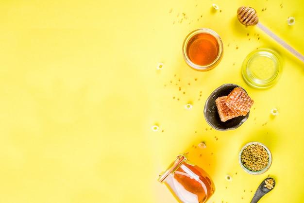 Organiczny kwiatowy miód, w słoikach, z pyłkami i plastrami miodu, z kreatywnym układem kwiatów, jasnym żółtym tle widok z góry kopia przestrzeń