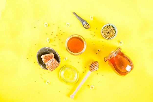 Organiczny kwiatowy miód, w słoikach, z pyłkami i plastrami miodu, z widokiem na kwiaty polne