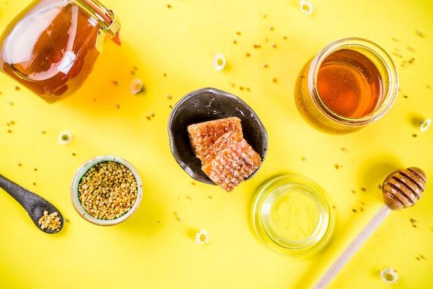Organiczny kwiatowy miód, w słoikach, z pyłkami i plastry miodu, z kreatywnym układem polnych kwiatów jasnożółta ściana