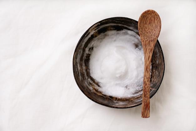 Organiczny olej kokosowy w misce kokosowej z łyżeczką kokosową. koncepcja zrównoważonego rozwoju. widok z góry. flat lay.