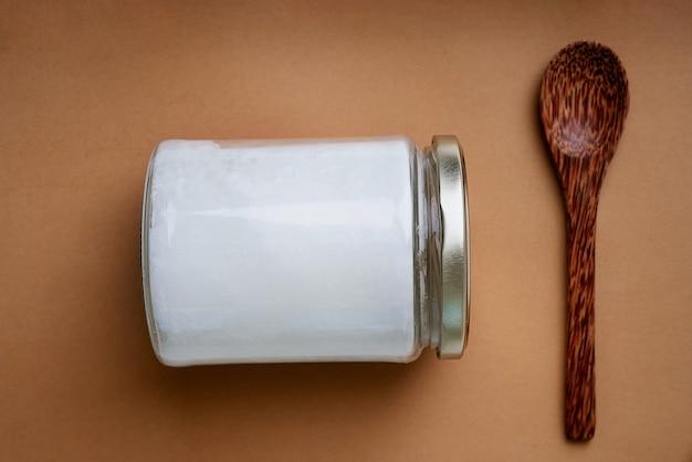 Organiczny olej kokosowy w szklanym słoiku z łyżeczką kokosową. koncepcja zrównoważonego rozwoju. widok z góry. flat lay.
