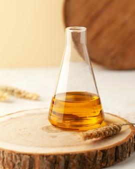 Organiczny olej roślinny w szklanej kolbie na drewnianym stojaku z kłoskami pszenicy z miejscem na tekst