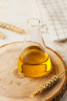 Organiczny olej roślinny w szklanej kolbie na drewnianym stojaku z kłoskami pszenicy