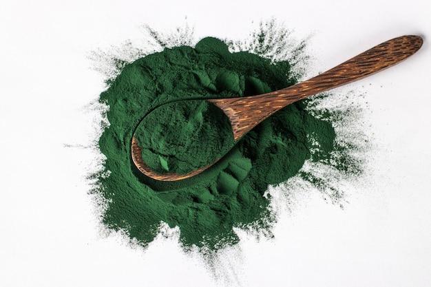 Organiczny proszek spiruliny z alg w drewnianą łyżką na białym tle.