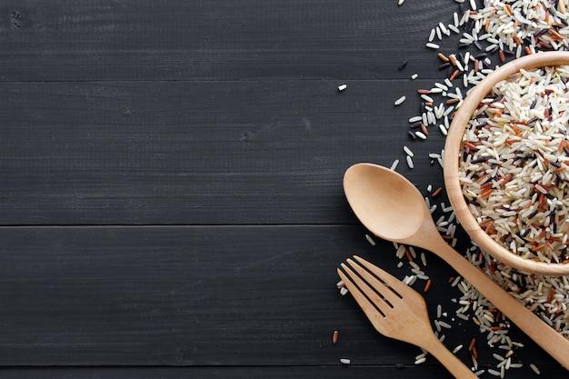 Organiczny riceberry, czerwony ryż jaśminowy i brązowy ryż (ryż hommali) z drewnianą łyżką na czarnym tle drewnianych