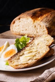 Organiczny rzemieślniczy chleb na zakwasie i jajka na twardo w białej płytce