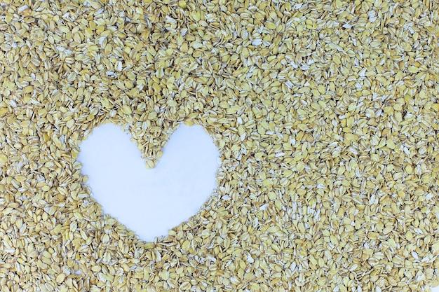 Organiczny surowy owies walcowany w kształcie serca.