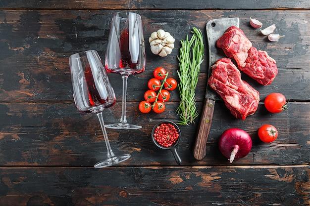 Organiczny surowy stek wołowy chuck eye roll nad starym tasakiem rzeźniczym w pobliżu kieliszków do czerwonego wina z ziołami i przyprawami na starym ciemnym drewnianym stole. widok z góry z miejscem na tekst.