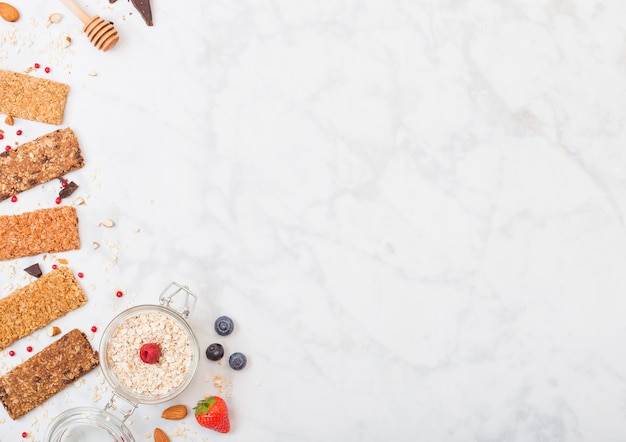 Organiczny zbożowy bar muesli z jagodami z miodową łyżką i słojem owsa na marmuru stole odgórny widok. truskawka, malina i jagoda z orzechami migdałów.