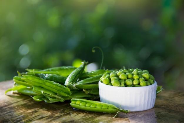 Organiczny zielony groszek w białej misce na naturalnym zielonym tle
