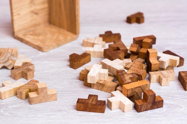 Organizacja i porządek. drewniane elementy układanki leżą w bałaganie obok składanej formy.