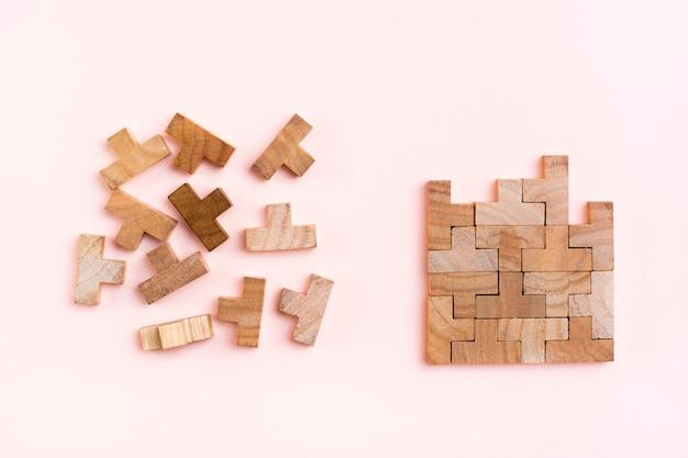Organizacja i porządek. drewniane elementy układanki są ułożone prawidłowo i chaotycznie rozrzucone w nieładzie